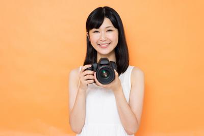 カメラを持つ笑顔の女性